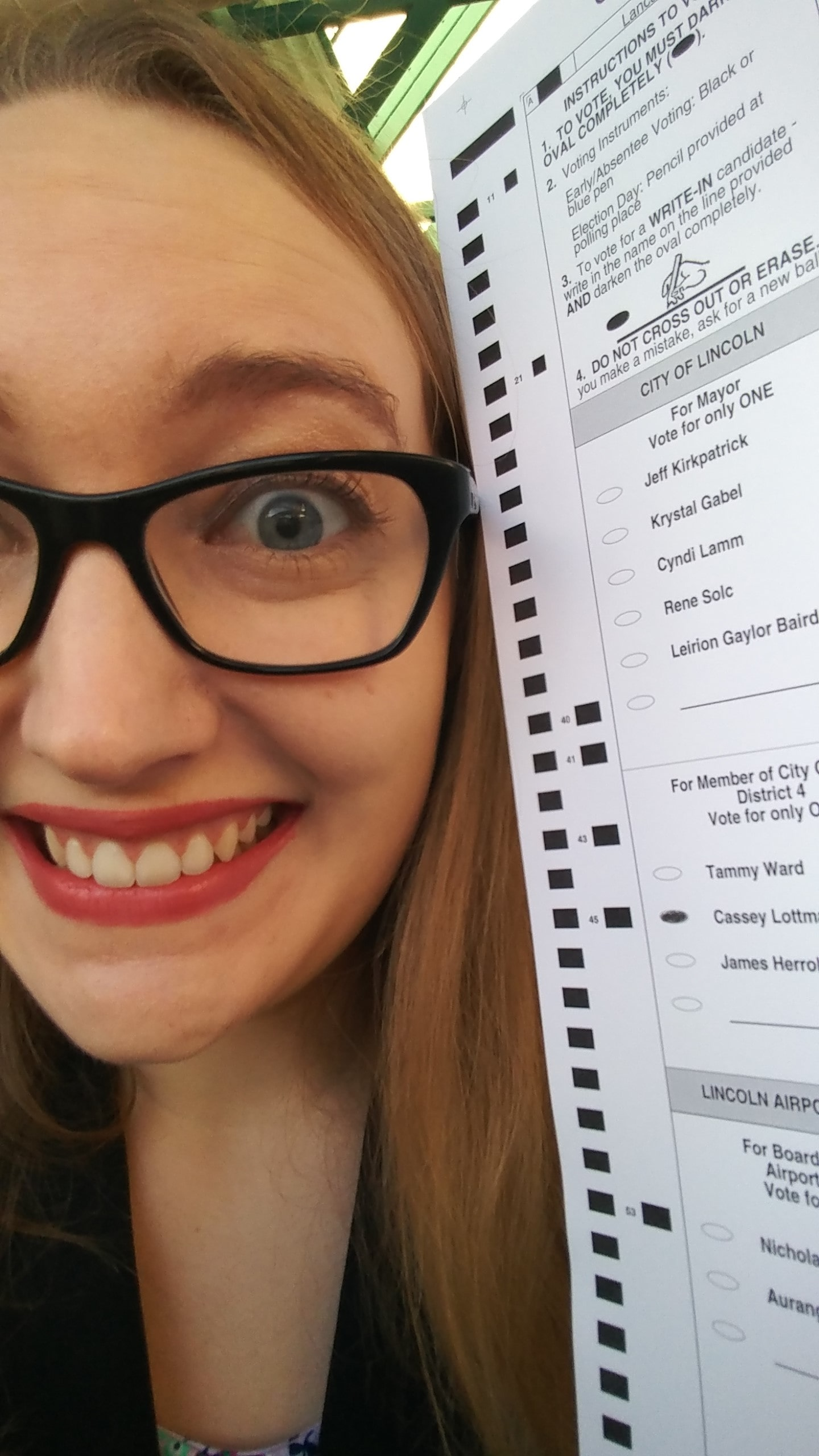 A close-up of Cassey's very excited face. She's holding a ballot with her own name on it, with the bubble filled in.