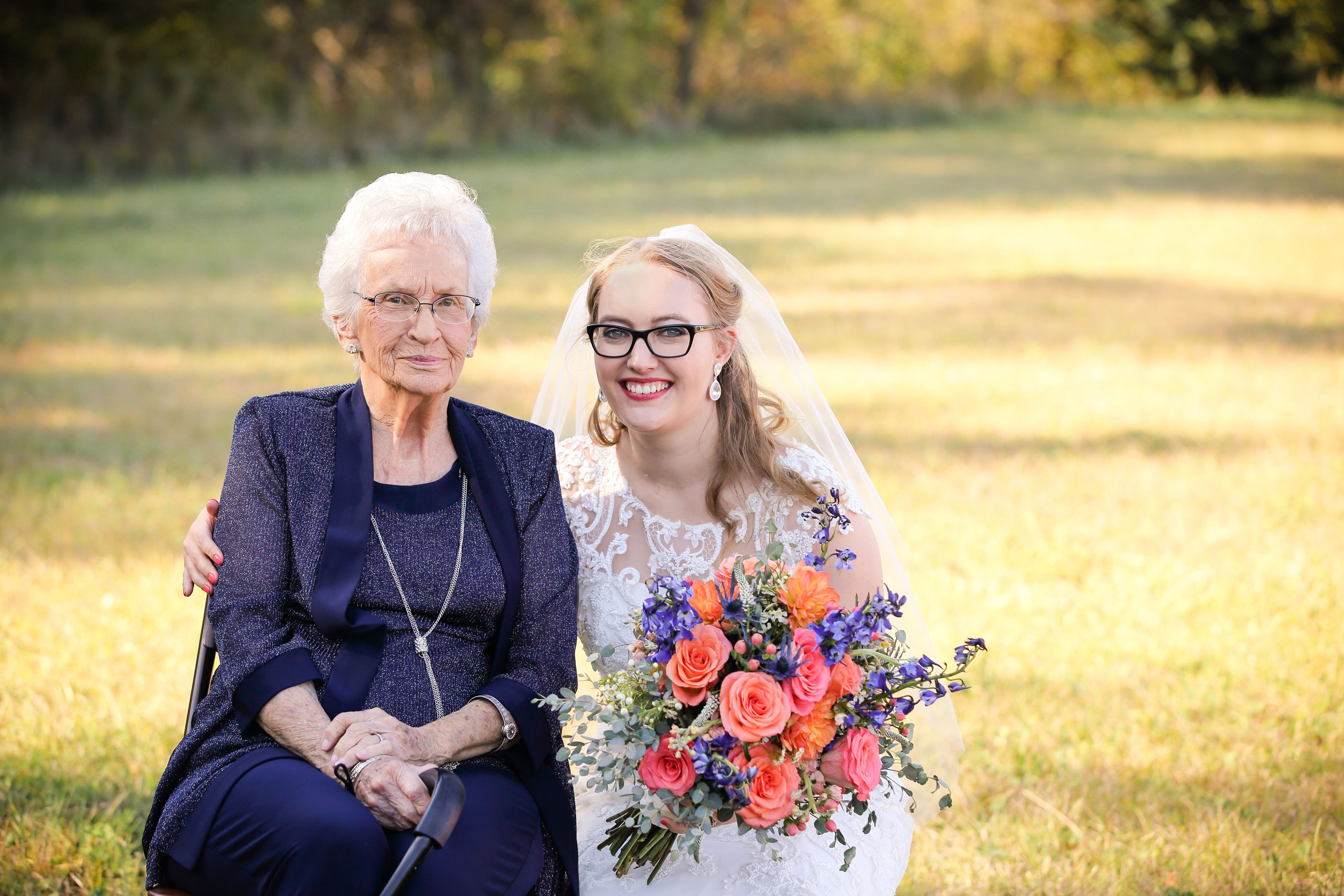 Cassey, in a wedding dress, embraces a well-dressed elderly woman